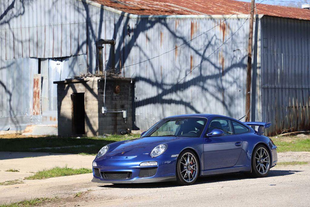 Porsche 997 GT3 in front of an old metal building
